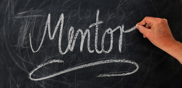 """Photo of a hand writing the word """"Mentor"""" in a cursive script in chalk on a blackboard"""